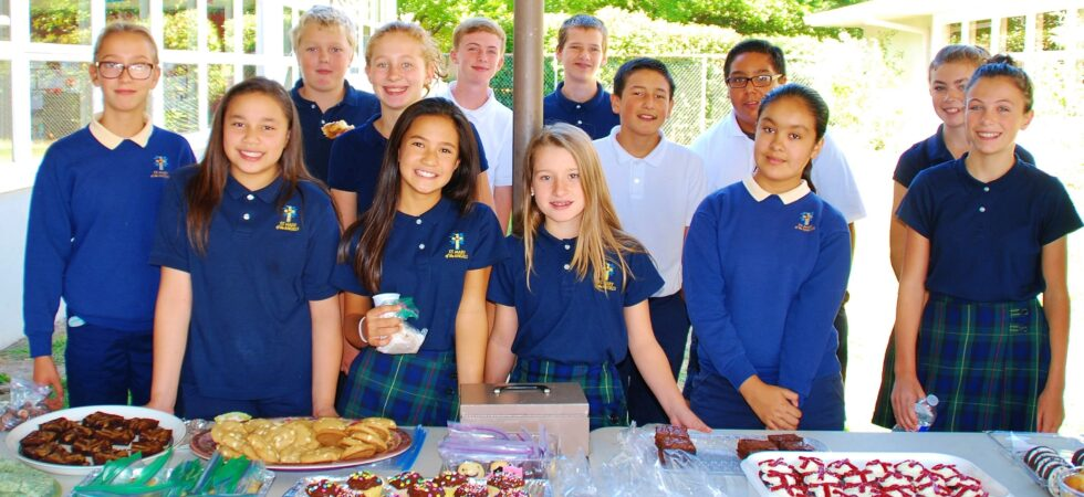 children standing by the bake sale table