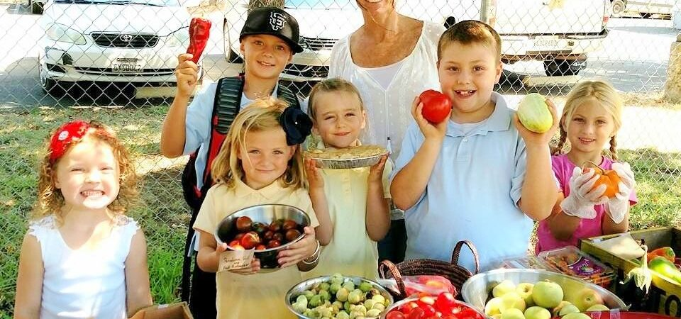 Children holding produce at the gardening sale